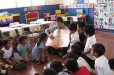"Save the Children staff working the education strategy ""reading out loud"" at a rural school. Photo Michael Bisceglie"